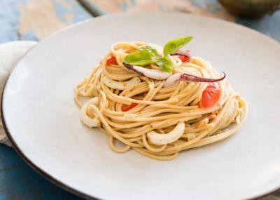 Espaguetis integrales con pesto, calamares y tomates cherry